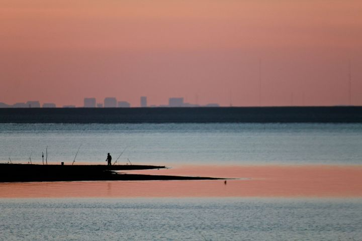 Alone at the shoreline; the distance skyline reminds us how close we are to the city....