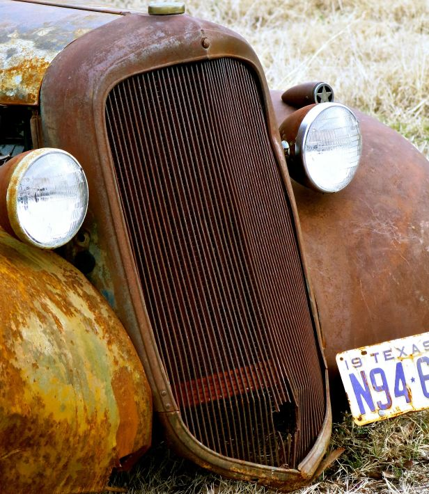 "The front grill of a 1940  truck (according to the ""antique car ""tag) slowly succumbs to the rusting and weathering elements of a Texas climate…."
