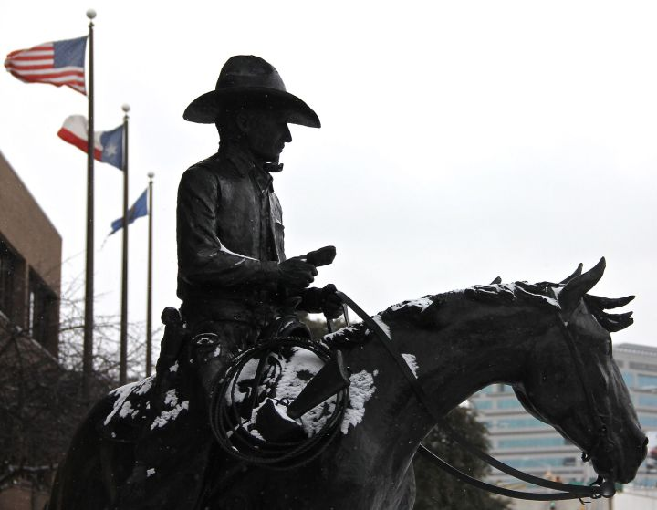 A light snow, appropriately enough, dusts the cowboy statue in from of the Texas and Southwestern Cattle Raisers Foundation building in Fort Worth. Real Cowboys (back then) endured a whole lot harsher weather than this….