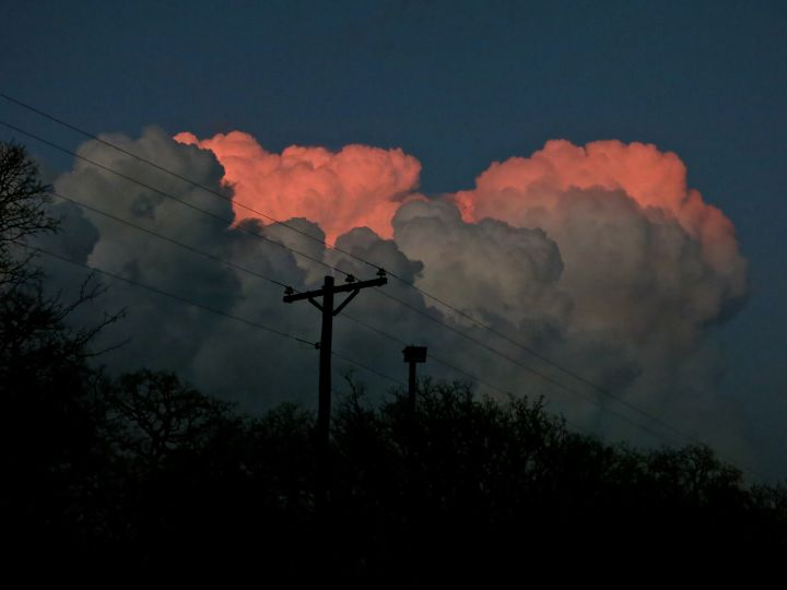An impressive, late evening thunderstorm rises above the tree line near the house….