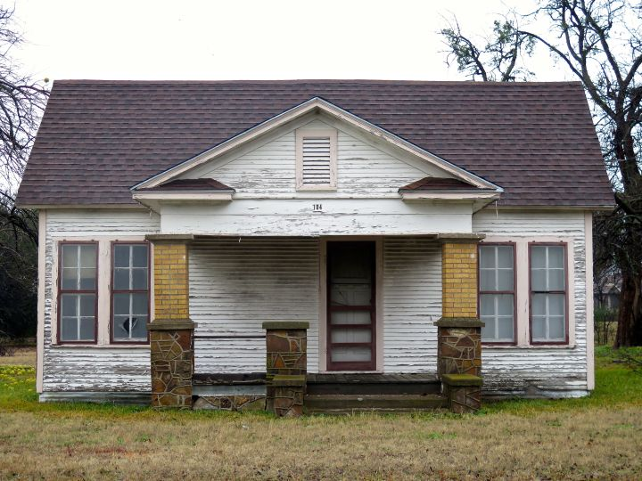 """I have watched """"this old house"""" deterriorate for years and figured before it falls in on itself, it was worthy of a photograph. It is odd decisions like this: symmetry in everything except the front door and a porch column that makes me wonder about decisions made in its design and construction many years ago."""